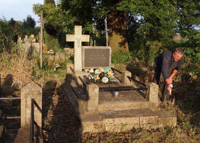Henryk Sawka porządkuje grób Władysława Kołaczkowskiego, fot. Krzysztof Czarnota