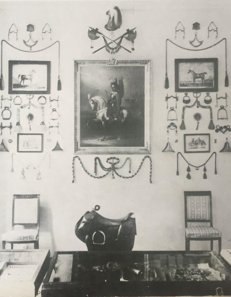 """Fragment wystawy przygotowanej przez Andrzeja Grzybowskiego, jedna ze ścian z charakterystyczną dekoracją wokół """"Husarza"""" Januara Suchodolskiego, źródło: Koń Polski 1 (73), 1984"""